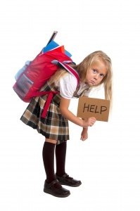 little girl carrying very heavy backpack or schoolbag full